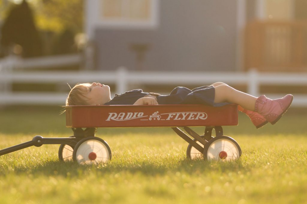 Young child laying in a Radio Flyer wagon in the lawn at sunset