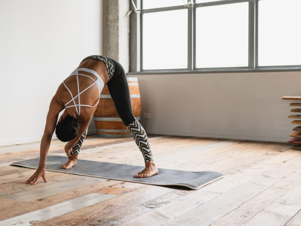 Woman leaning forward in yoga pose in a well-lit sparse room with wooden floor