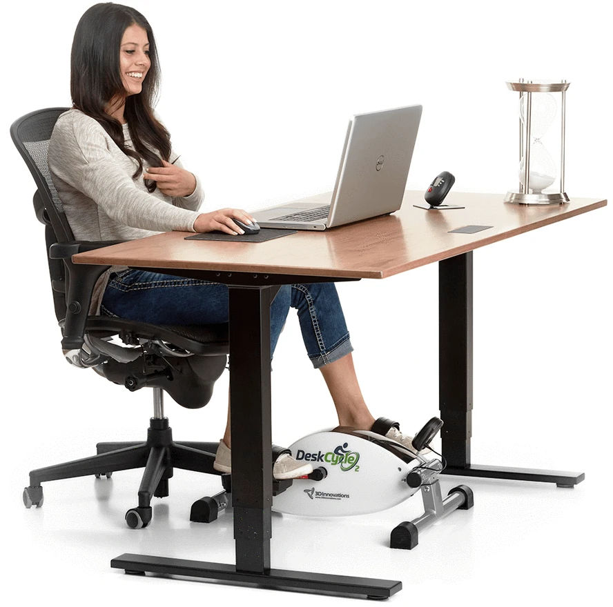 Dark-haired woman sitting at a desk with a laptop and large hourglass on top, with a miniature pedal-based workout tool on the floor