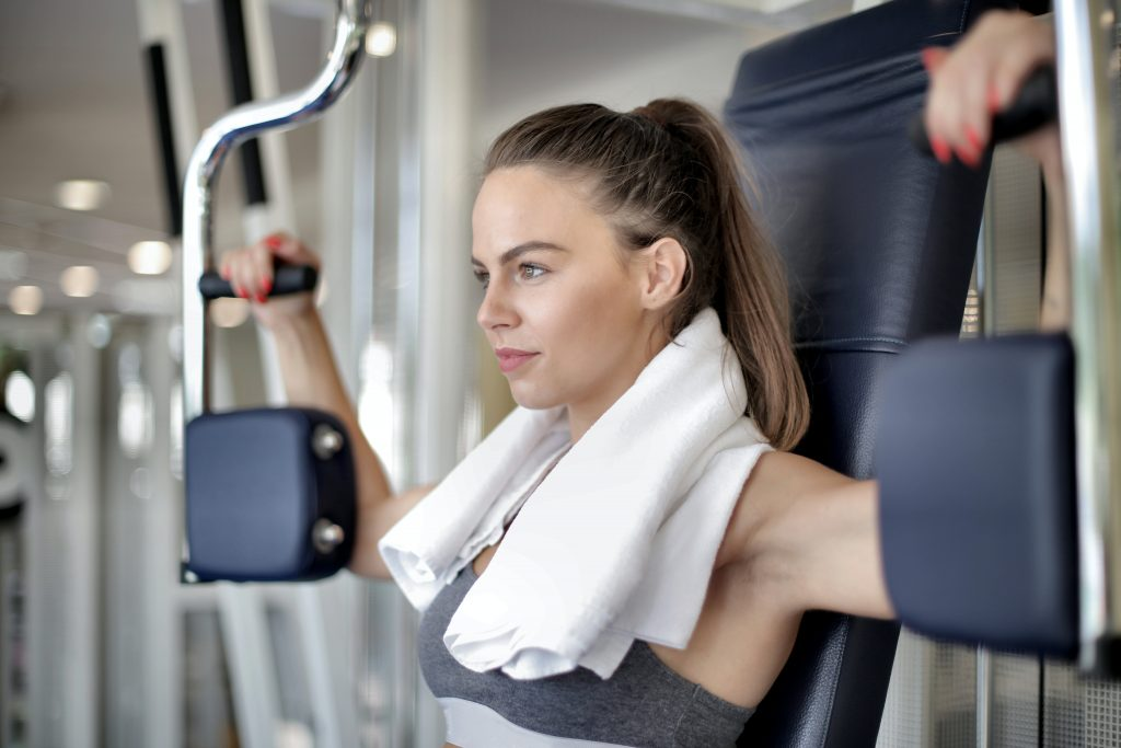 Blonde woman with a towel around her neck sitting on a machine doing upper body workouts