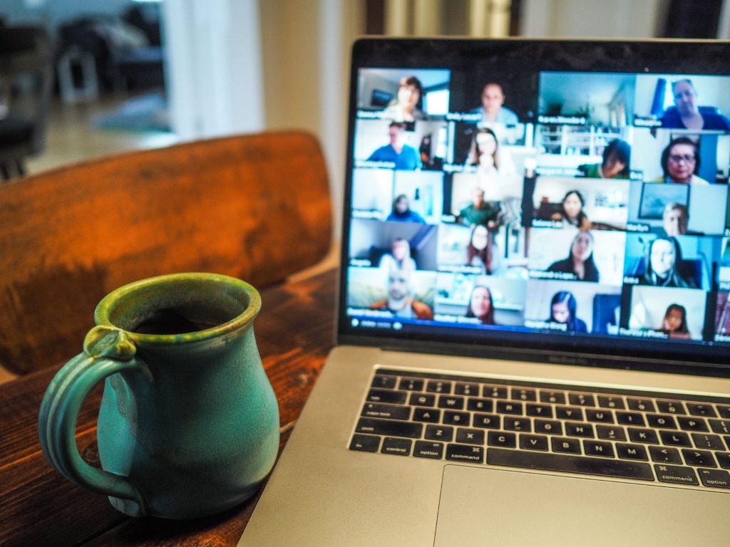 Laptop computer on table hosting a large group video call, with a ceramic mug nearby