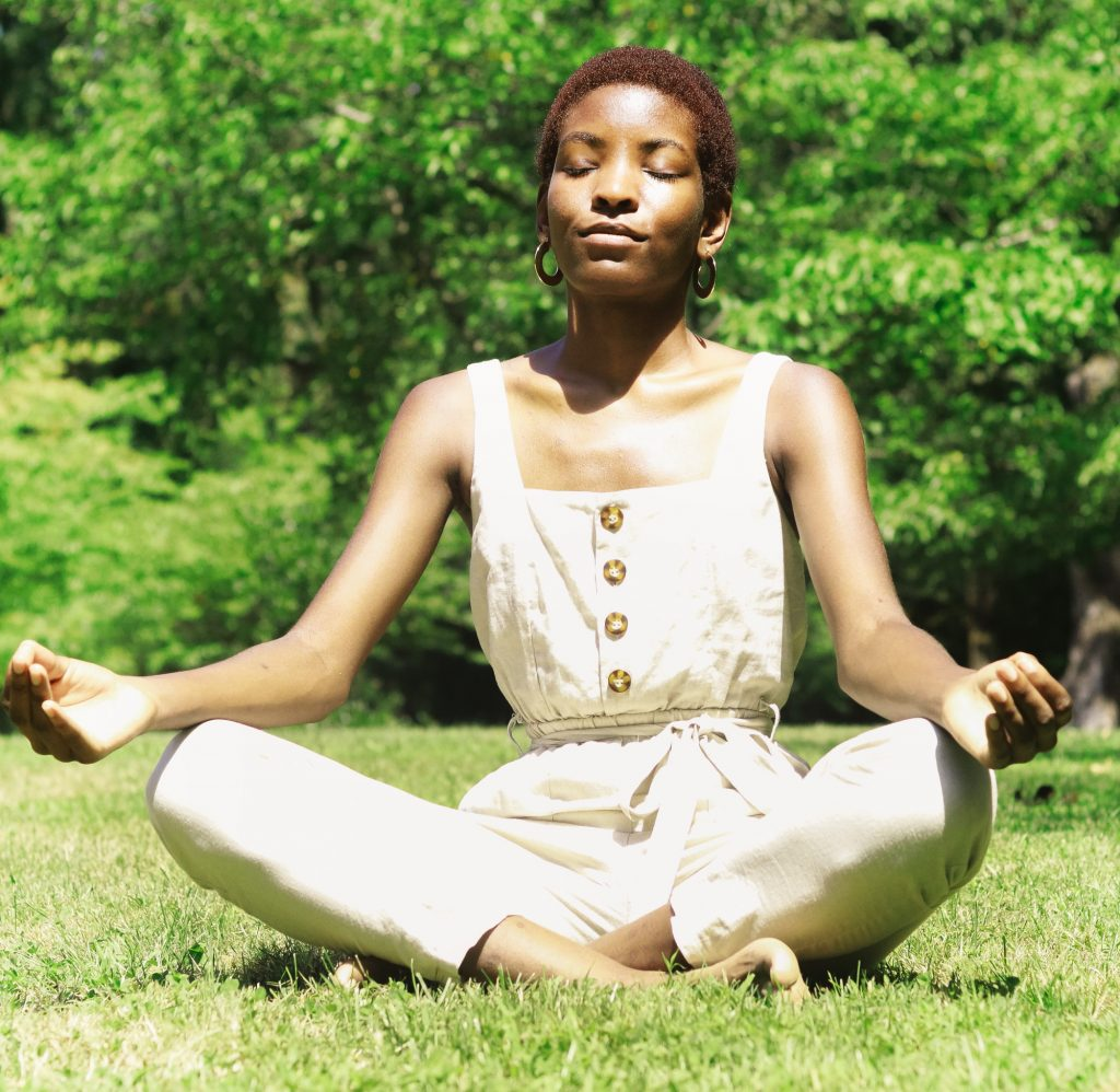 Black woman with tan outfit sitting cross-legged in grass meditating