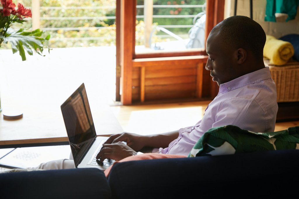 Man at Home on his Couch Working on Laptop