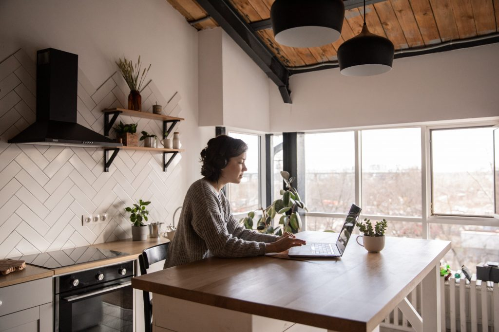 Woman Seated at Kitchen Counter Working on Laptop