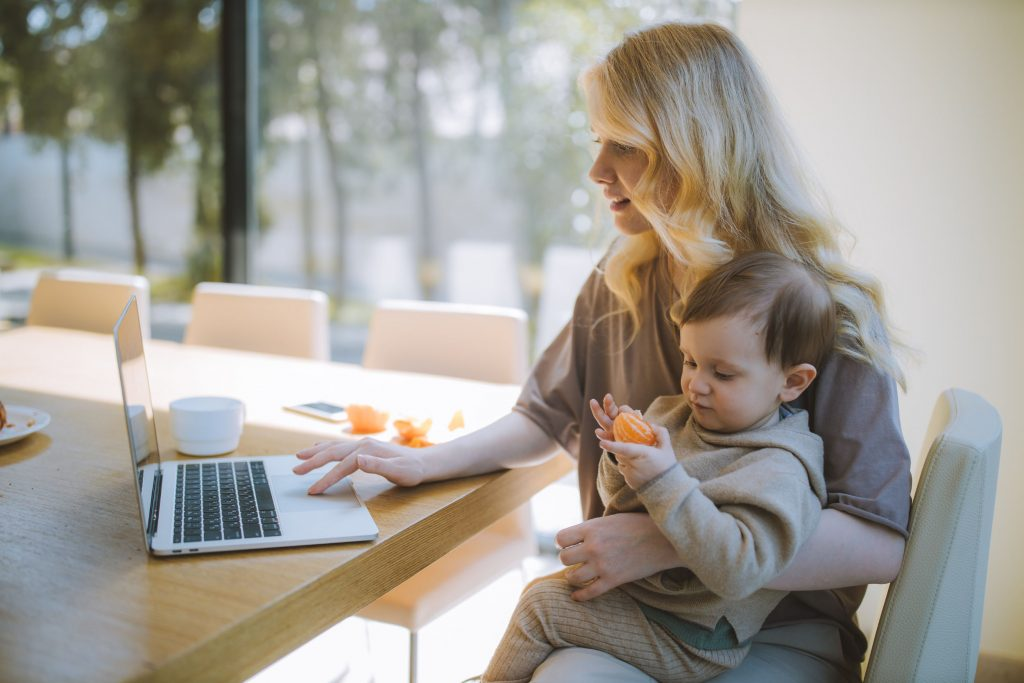 Woman Working at Home Holding Baby on Her Lap