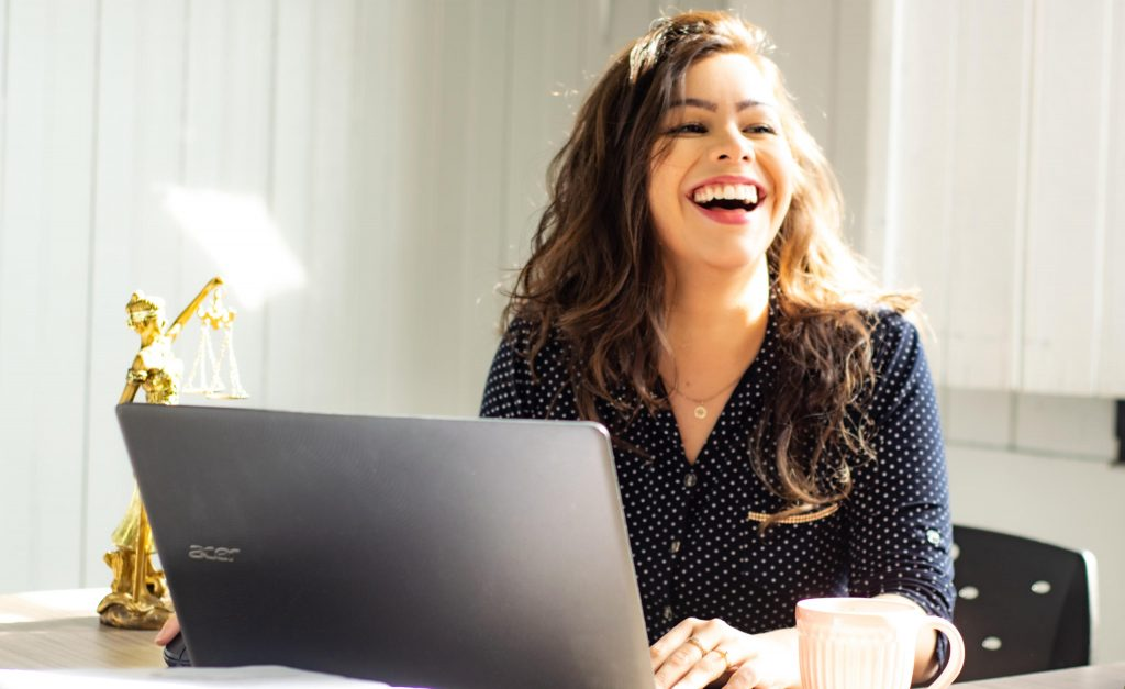 Happy professional woman at laptop computer.